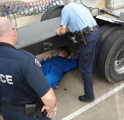 Officers inspect the brakes and tires on a driver's trailer.