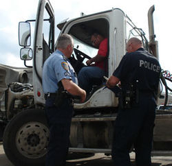 Officers Michael Trautwein (left) and Keith Bell (right), of the Houston and Pasadena police departments, check a driver's permits and logbook.