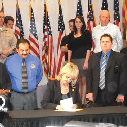 Arizona Governor Jan Brewer signs SB 1070 into law.