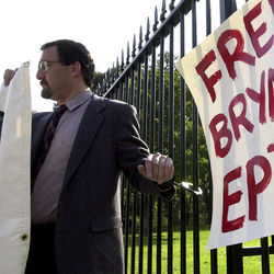 Medical marijuana supporter Bruce Mirken stands handcuffed to the fence at the White House in 2002.
